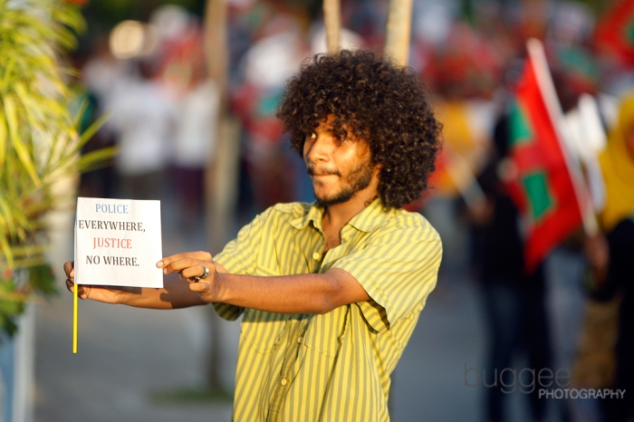 A supporter of former President Mohamed Nasheed holds a placard condemning police brutality in a demonstration shortly after his resignation on February 7.